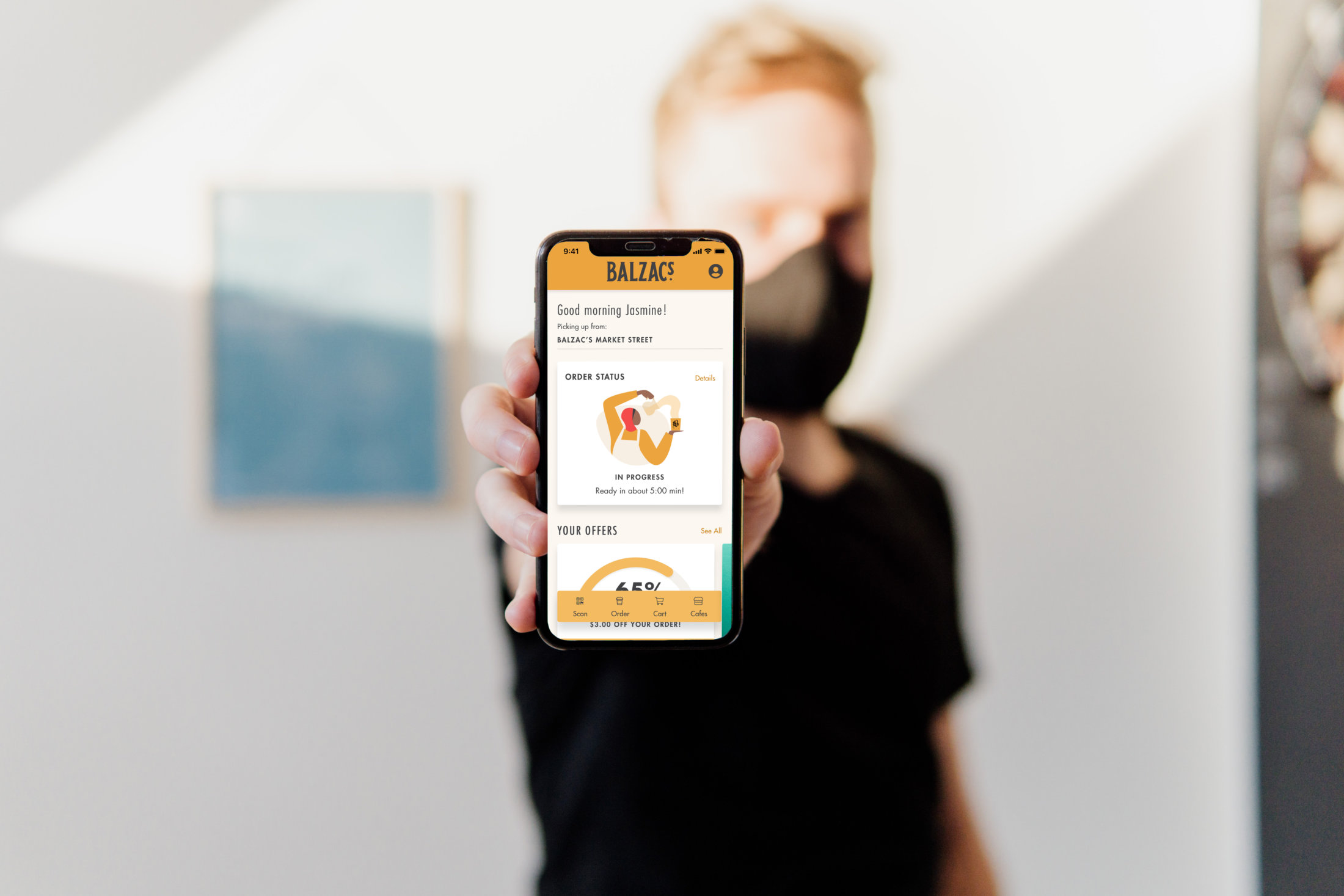 A person holding a phone that shows the Balzac's Coffee Roasters app